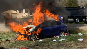 A man was taken to hospital after his vehicle rolled over and caught fire in the city's south end Tuesday. (Ottawa Fire Service)