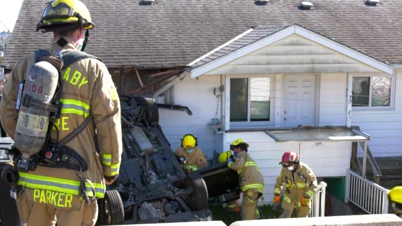 First responders say an 80-year-old woman crashed her car into her Burnaby home on April 12, 2021.