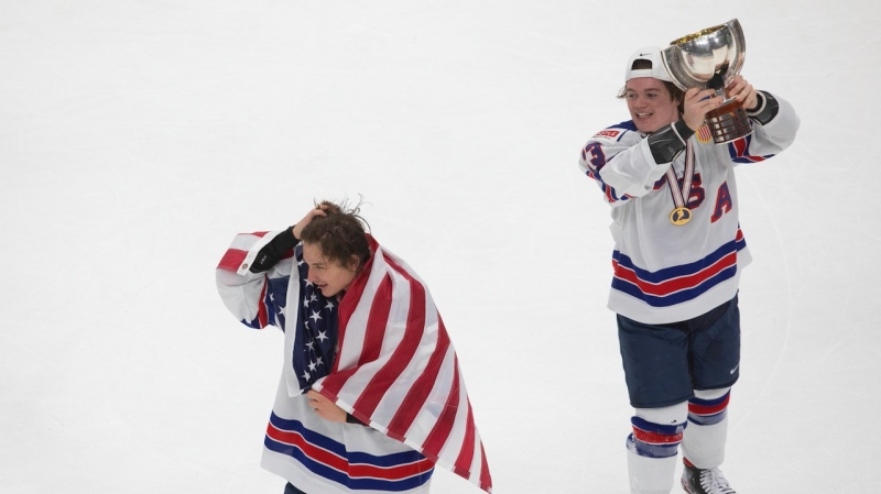 United States' Trevor Zegras, left, wears his country's flag as Cole Caufield hoists the trophy after defeating Canada in IIHF World Junior Hockey Championship gold medal game action in Edmonton on Tuesday, January 5, 2021. THE CANADIAN PRESS/Jason Franson