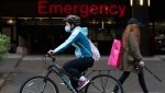 A woman wears a protective face covering to help prevent the spread of COVID-19 as she bikes past the emergency entrance of Vancouver General Hospital in Vancouver, B.C., Friday, April 9, 2021. COVID-19 cases have been on a steady increase in the province of British Columbia over the past week. THE CANADIAN PRESS/Jonathan Hayward