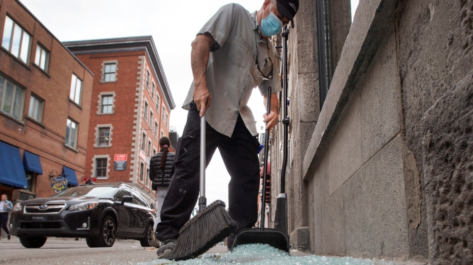Carlos Londono cleans up broken glass after an anti-COVID-19 curfew riot on Monday, April 12, 2021 in Montreal. THE CANADIAN PRESS/Ryan Remiorz