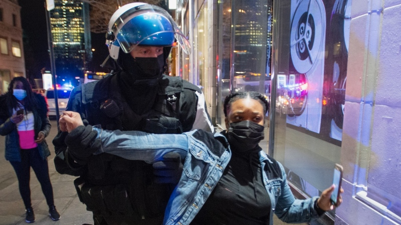Police try and detain a woman as anti-curfew protests continue for a second night Monday, April 12, 2021 in Montreal.THE CANADIAN PRESS/Ryan Remiorz