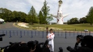 Former Olympian Aya Terakawa poses for the media before she carries the torch during the first day of the Osaka round at a former Expo site in Suita, north of Osaka, Japan, on April 13, 2021. (Hiro Komae / AP)