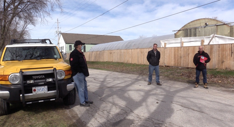 Residents in Vanastra, Ont. stand near a marijuana greenhouse they say is the source of a foul odour. (Scott Miller / CTV News)