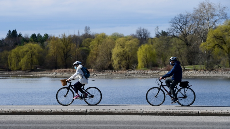 Masked cyclists make their way along the edge of Dow's Lake as the third wave of the COVID-19 pandemic grips Ottawa on Tuesday, April 13, 2021. (Sean Kilpatrick/THE CANADIAN PRESS)