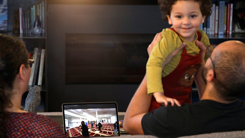 FILE - Ahmad Kamel lifts his son Yusuf Kamel, 2, as his wife Nadia Chaouch sits next to them as the family watches a live stream of previous day's Taraweeh prayer from the nearly empty Muslim Association of Puget Sound mosque as they wait to break the Ramadan daily fast in their home during the coronavirus outbreak in Seattle. (AP Photo/Elaine Thompson, File)