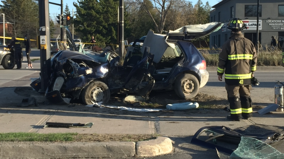 Firefighters cut away the roof of a vehicle following a serious crash on First Street in Collingwood, Ont. on Tues. April 13, 2021 (Roger Klein/CTV News)