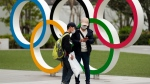 A boy looks at a cellphone after his mother took pictures of him in front of a display of the Olympic rings at the Japan Olympic Museum in Tokyo on Friday, April 2, 2021. (AP Photo/Hiro Komae)