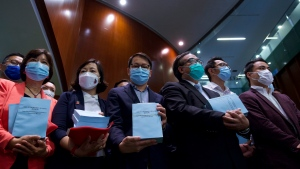 """Pro-China lawmakers pose to reporters after attending the first and second reading of """"Improving Electoral System (Consolidated Amendments) Bill 2021"""" at the Legislative Council in Hong Kong, Wednesday, April 14, 2021. (AP Photo/Vincent Yu)"""
