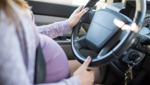 This stock image shows a pregnant woman driving a vehicle. (The University of British Columbia Okanagan campus)