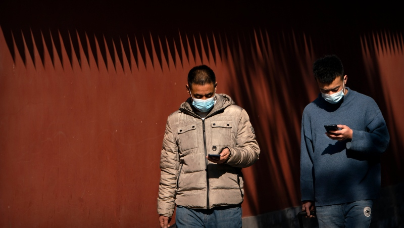 People wearing face masks to protect against the spread of the coronavirus use their smartphones as they walk through Ditan Park in Beijing, Tuesday, Feb. 9, 2021. (AP Photo/Mark Schiefelbein)
