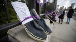A written message is seen attached to a pair of shoes hung on the Burrard Bridge in remembrance of victims of illicit drug overdose deaths on International Overdose Awareness Day, in Vancouver, on Monday, August 31, 2020. THE CANADIAN PRESS/Darryl Dyck