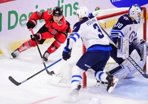 Ottawa Senators' Tim Stutzle (18) stops behind the net of Winnipeg Jets goaltender Laurent Brossoit (30) as Jets' Tucker Poolman (3) defends during second period NHL action in Ottawa on Wednesday, April 14, 2021. THE CANADIAN PRESS/Sean Kilpatrick
