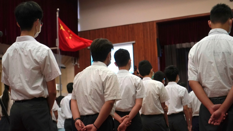 Students attend a flag raising ceremony during the National Security Education Day at a secondary school, in Hong Kong, Thursday, April 15, 2021. (AP Photo/Kin Cheung)