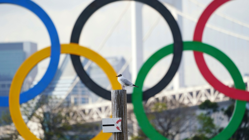 A bird rests with a backdrop of the Olympic rings floating in the water in the Odaiba section Thursday, April 8, 2021, in Tokyo. (AP Photo/Eugene Hoshiko)