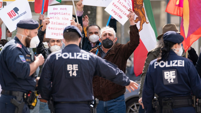 Protestors of an Iranian opposition group and police officers stand near the the 'Grand Hotel Wien' in Vienna, Austria, Friday, April 9, 2021 where closed-door nuclear talks with Iran take place. (AP Photo/Florian Schroetter)