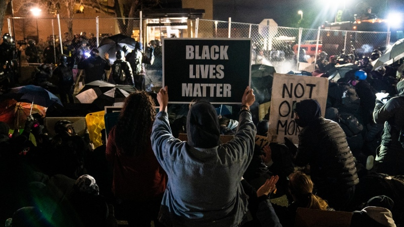 Demonstrators take part in a protest over the fatal shooting of Daunte Wright during a traffic stop, outside the Brooklyn Center Police Department, on April 14, 2021. (John Minchillo / AP)