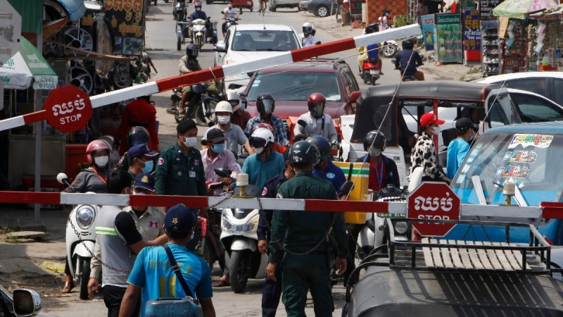 People are blocked by local police officers to get into the main city street near Phnom Penh International airport in Phnom Penh, Cambodia, on April 15, 2021. (Heng Sinith / AP)