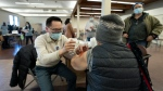 Dr. E. Kwok administers a COVID-19 vaccine to a recipient at a vaccination clinic run by Vancouver Coastal Health, in Richmond, B.C., Saturday, April 10, 2021. THE CANADIAN PRESS/Jonathan Hayward