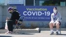 People wait outside a COVID-19 vaccination clinic at the Martin Brodeur Arena in Montreal, on Tuesday, April 13, 2021. THE CANADIAN PRESS/Paul Chiasson