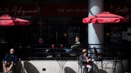 People sit on a patio outside a cafe in Vancouver, on Sunday, April 11, 2021. THE CANADIAN PRESS/Darryl Dyck