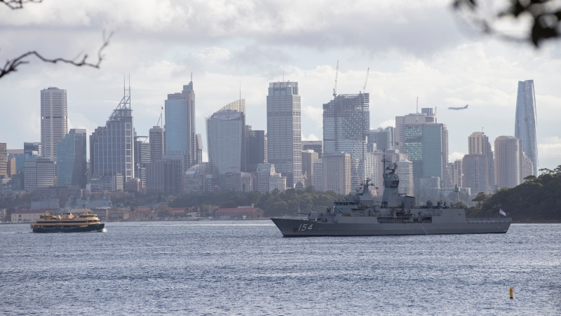 The Manly ferry, left, sails across the Sydney harbour towards HMAS Arunta, an Anzac-class frigate of the Royal Australian Navy in Sydney, Australia, Tuesday, April 6, 2021. (AP Photo/Mark Baker)