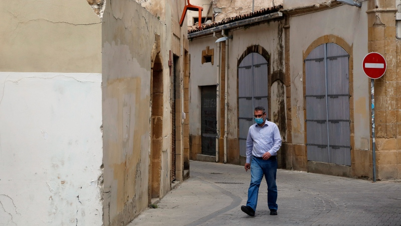 A man wearing a face mask to protect against the spread of coronavirus, walks at the old town of divided capital Nicosia, Cyprus, Friday, April 9, 2021. (AP Photo/Petros Karadjias)