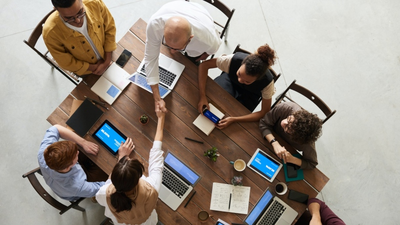 A stock image of people shaking hands and sitting around a conference table. (Pexels, fauxels)