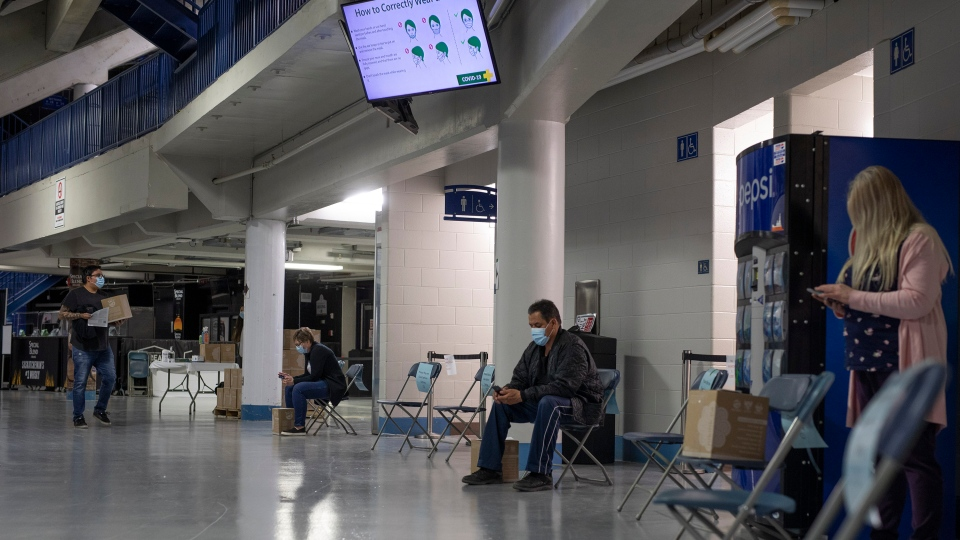 Patients wait in a designated area after receiving their shot at the Saskatoon Tribal Council run vaccination clinic inside SaskTel centre in Saskatoon, Sask., on Thursday, April 15, 2021. THE CANADIAN PRESS/Kayle Neis
