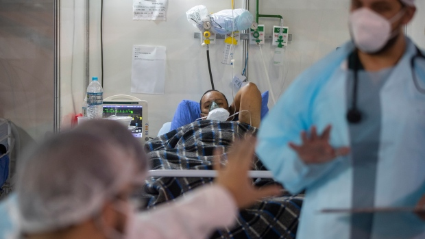 In this April 13, 2021, file photo, health workers exchange information as COVID-19 patient Everton Nascimento de Oliveira, 32, lies in an emergency unit bed of a field hospital in Ribeirao Pires, greater Sao Paulo area, Brazil. (AP Photo/Andre Penner, File)