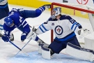 Toronto Maple Leafs' Wayne Simmonds (24) trips over the pad of Winnipeg Jets goaltender Connor Hellebuyck (37) during second period NHL hockey action in Toronto on Thursday, April 15, 2021. THE CANADIAN PRESS/Frank Gunn