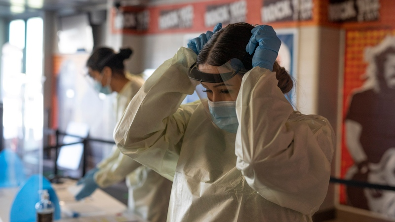 STC volunteer Montana Ledoux puts on PPE at the Saskatoon Tribal Council run vaccination clinic inside SaskTel centre in Saskatoon, Sask., on Thursday, April 15, 2021. THE CANADIAN PRESS/Kayle Neis