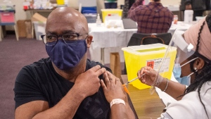 Eugene Anderson receives the Pfizer-BioNTech COVID -19 vaccine from Carolyne Aremo, RN, at the first vaccine clinic in an African Nova Scotia community, in Upper Hammonds Plains, N.S. on Thursday, April 8, 2021. THE CANADIAN PRESS/Andrew Vaughan