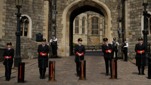 Wardens stand lined up, with police officers standing guard behind them outside the King Henry VIII Gate of Windsor Castle, in Windsor, England, Wednesday, April 14, 2021. (AP / Matt Dunham)