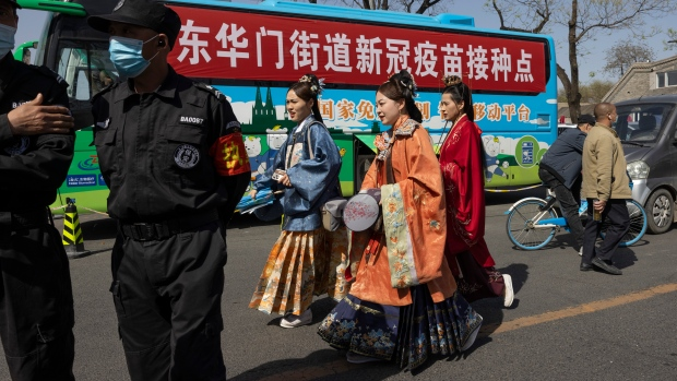 Residents in traditional costumes pass a bus offering free coronavirus vaccinations at an entrance to the Forbidden City in Beijing on Wednesday, April 14, 2021. (AP Photo/Ng Han Guan)