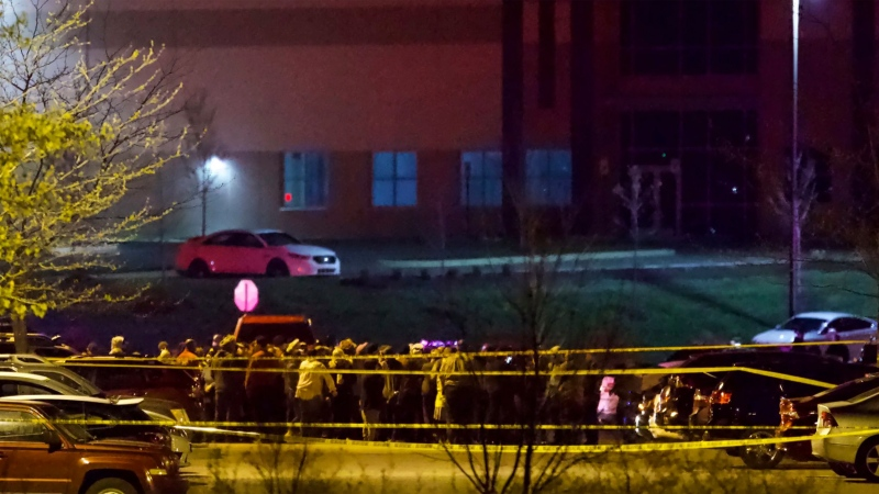 People stand outside a FedEx facility near Indianapolis International Airport after a shooting with multiple victims was reported late Thursday night, April 15, 2021. (Mykal McEldowney/The Indianapolis Star via AP)