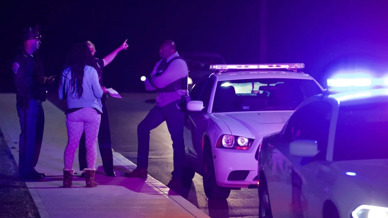 A woman asks law enforcement near the FedEx hub following a shooting in Indianapolis, IN., Friday, April 16, 2021. Multiple people were shot and killed in a late-night shooting at a FedEx facility in Indianapolis, and the shooter killed himself, police said.(Mykal McEldowney/The Indianapolis Star via AP)
