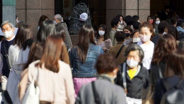 People wearing protective masks to help curb the spread of the coronavirus walk along a pedestrian crossing in Tokyo, on April 15, 2021. (Eugene Hoshiko / AP)