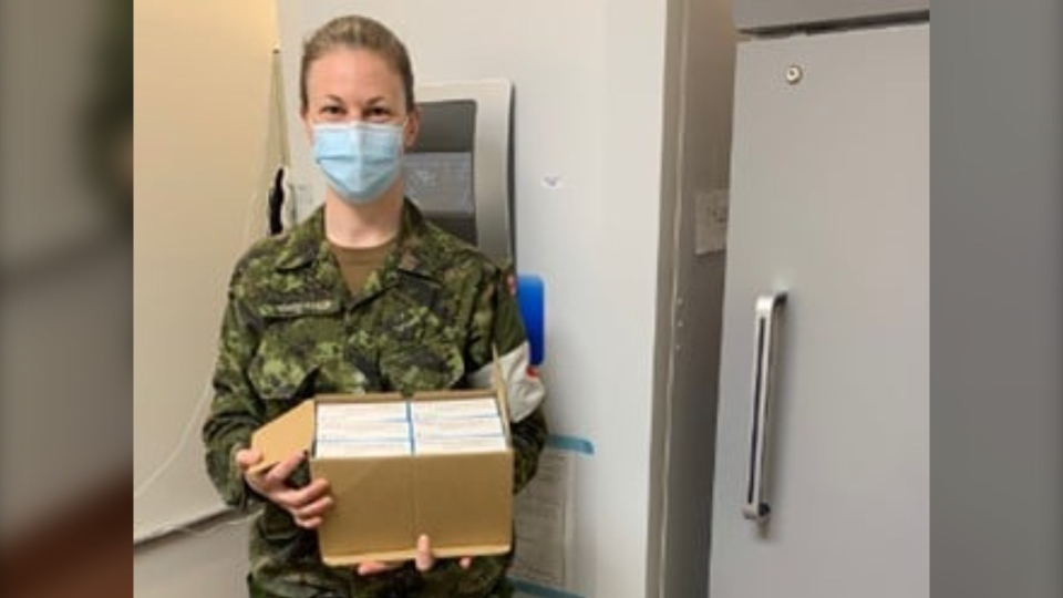 Capt. Megan Vanderveer, a pharmacy officer at Canadian Forces Health Services (Pacific), holds a box of newly arrived Moderna vaccines at CFB Esquimalt. (Maritime Forces Pacific)