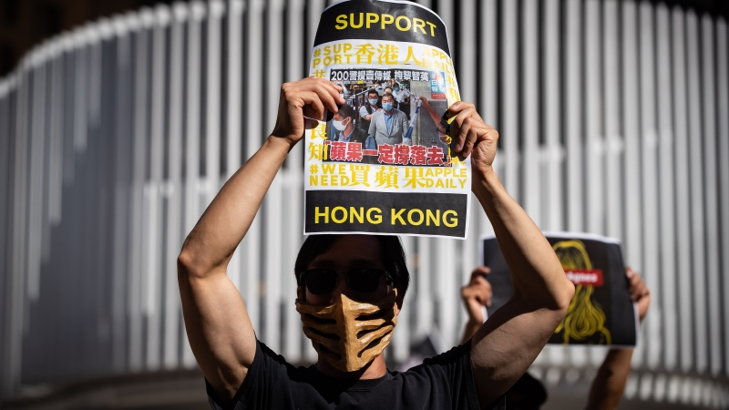 A man holds up a sign with a photograph of Hong Kong media tycoon Jimmy Lai, as people gather for a rally in support of Hong Kong democracy, in Vancouver, B.C., Sunday, Aug. 16, 2020. THE CANADIAN PRESS/Darryl Dyck