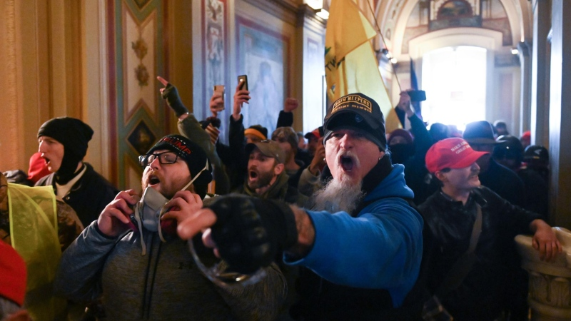 A man wearing an Oath Keepers hat yells in the hallways of the Capitol during the invasion by rioters on January 6. ROBERTO SCHMIDT/AFP/AFP via Getty Images
