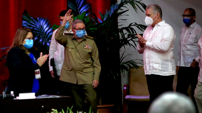 Raul Castro, first secretary of the Communist Party and former president, waves to members at the VIII Congress of the Communist Party of Cuba's opening session, as Cuban President Miguel Diaz-Canel, right, applauds at the Convention Palace, in Havana, Cuba, Friday, April 16, 2021. (Ariel Ley Royero/ACN via AP)