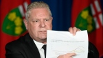 Ontario Premier Doug Ford points on a COVID-19 caseload projection model graph during a press conference at Queen's Park, in Toronto, Friday, April 16, 2021. Ontario is extending its stay-at-home order to six weeks, restricting interprovincial travel and limiting outdoor gatherings in an effort to fight a losing battle with COVID-19. THE CANADIAN PRESS/Frank Gunn