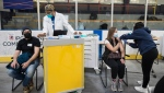 COVID-19 vaccine recipients are photographed at the Downsview Arena vaccination site, in Toronto, Friday, April 16, 2021. THE CANADIAN PRESS/Tijana Martin