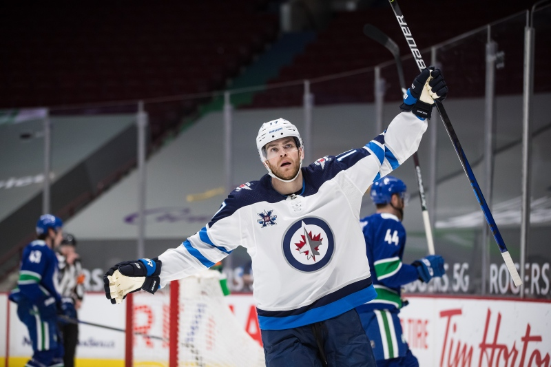 Winnipeg Jets' Adam Lowry celebrates his second goal during the third period of an NHL hockey game against the Vancouver Canucks, in Vancouver, B.C., Monday, March 22, 2021. THE CANADIAN PRESS/Darryl Dyck