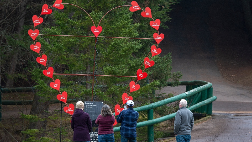 Visitors pay their repects at a memorial honouring the victims of the April 2020 murder rampage in rural Nova Scotia, in Victoria Park in Truro, N.S. on Tuesday, April 13, 2021. The Broken Heart Sculpture was built by Wayne Smith whose stepson Corrie Ellison was killed in the tragedy. THE CANADIAN PRESS/Andrew Vaughan
