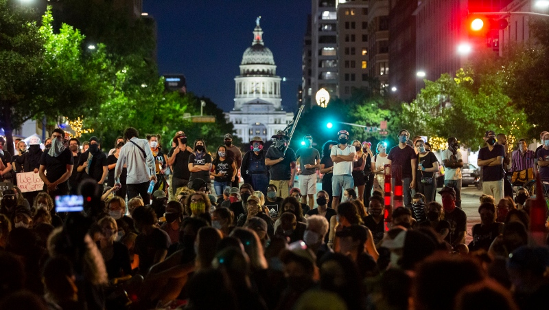 Hundreds of people gather for a vigil in memory of Garrett Foster on Sunday, July 26, 2020, in Austin, Texas. Police have identified Foster as the armed protester who was shot and killed by a person who had driven into a crowd at a demonstration Saturday against police violence. (Ana Ramirez/Austin American-Statesman via AP)