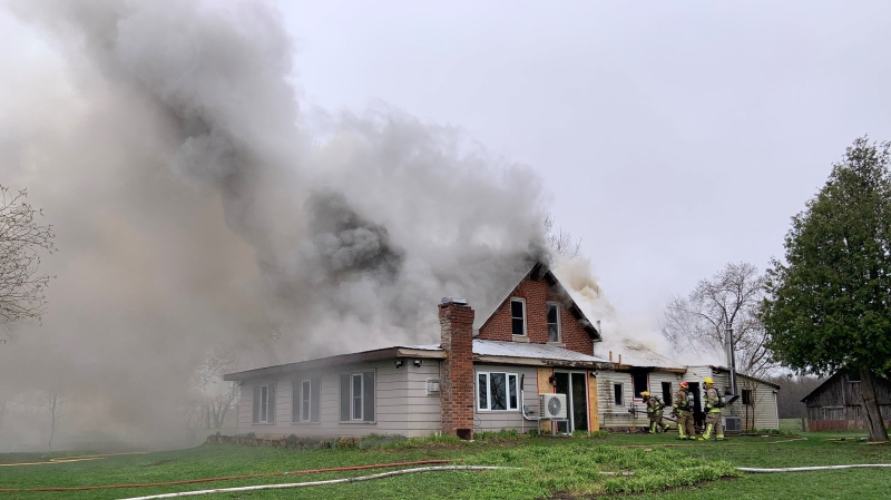 Firefighters work to put out a fire at a home on Vespra Valley Road in Springwater, Ont. on Fri. April 16, 2021 (Supplied)