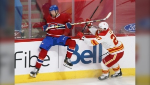 Montreal Canadiens' Brett Kulak avoids a hit from Calgary Flames' Josh Leivo during third period NHL hockey action in Montreal on Friday, April 16, 2021. Montreal defeated the Flames 2-1. (THE CANADIAN PRESS/Paul Chiasson)