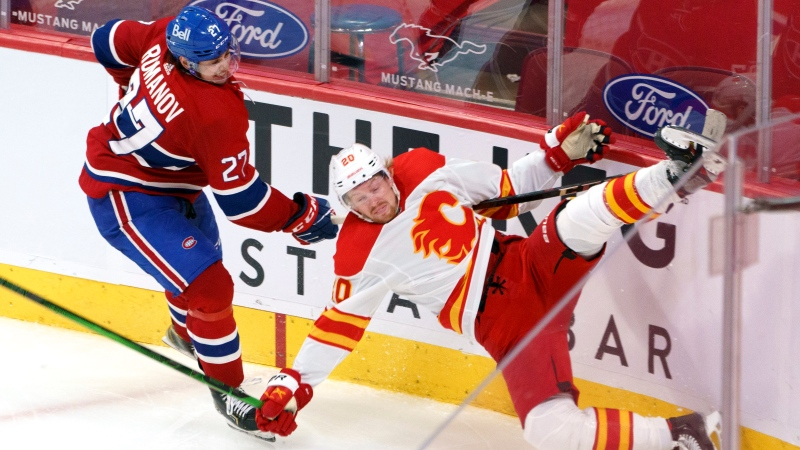 Calgary Flames' Joakim Nordstrom takes a hit from Montreal Canadiens' Alexander Romanov during third period NHL hockey action in Montreal on Friday, April 16, 2021. THE CANADIAN PRESS/Paul Chiasson